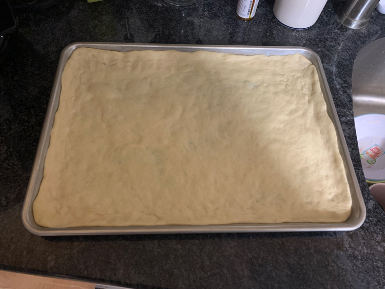 pre-baked pizza dough in a half-sheet pan