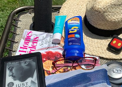 book, suntan lotion, beach hat, on an outdoor table