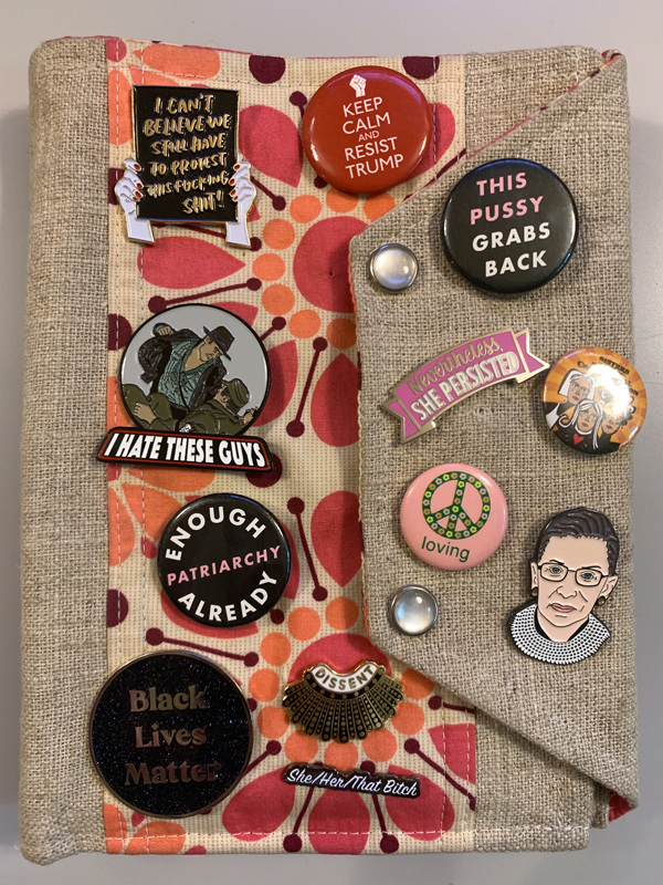 a fabric folio with sassy political pins on it