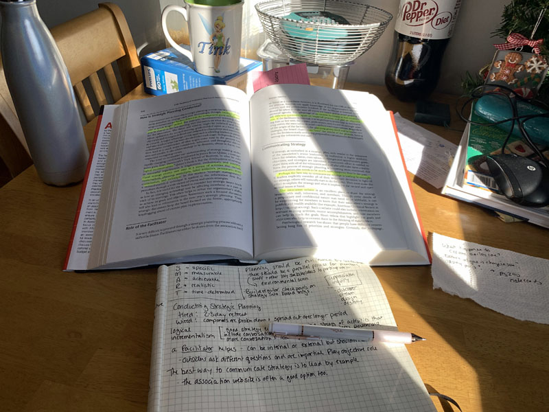 a text book and notebook on a kitchen table with sunlight streaming in