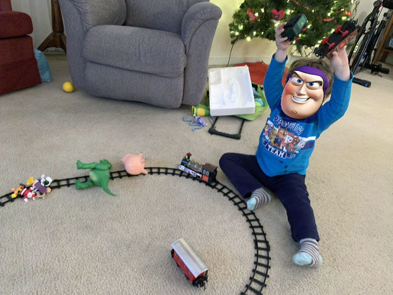 tiny diabolical child with his toys on a train track