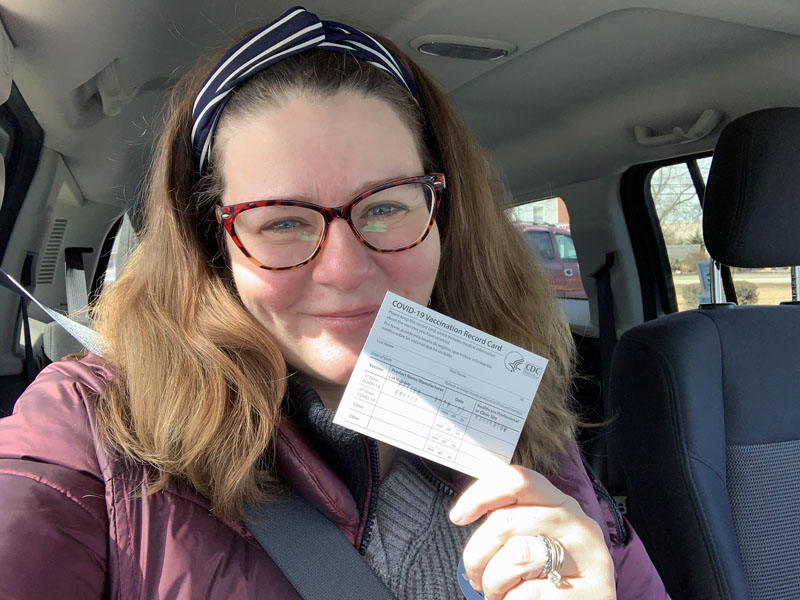 kim, happily holding up a covid vaccination card