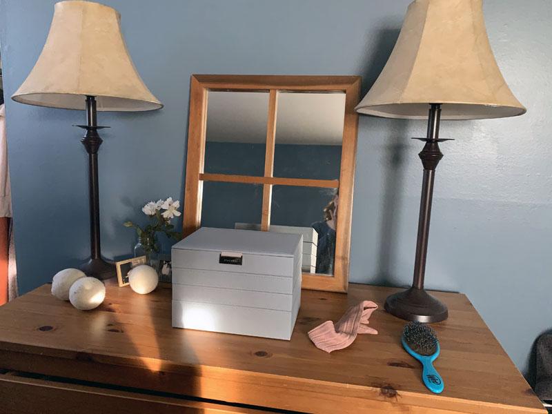 image of tidy dresser with jewelry box, brush, headband, and dryer balls.