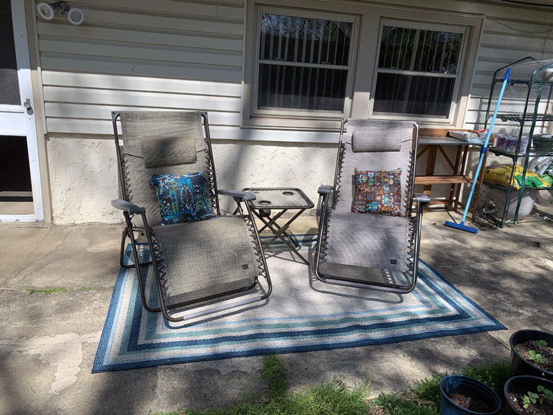 a patio, with 2 chairs, a table, and a patio rug, and a bunch of junk in the background that I can't get rid of.