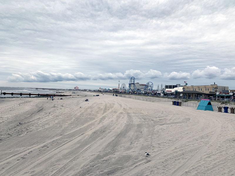 shot of a mostly empty beach, boardwalk behind it, heavy gray clouds