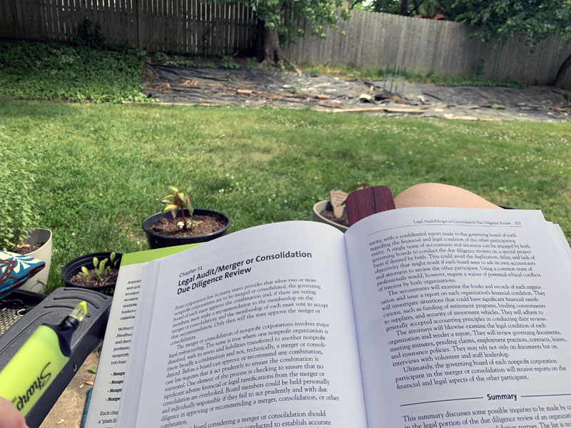 A gripping photo of an Association Law book open to the chapter about Due Diligence Review of a Merger or Consolidation. And my crummy lawn.