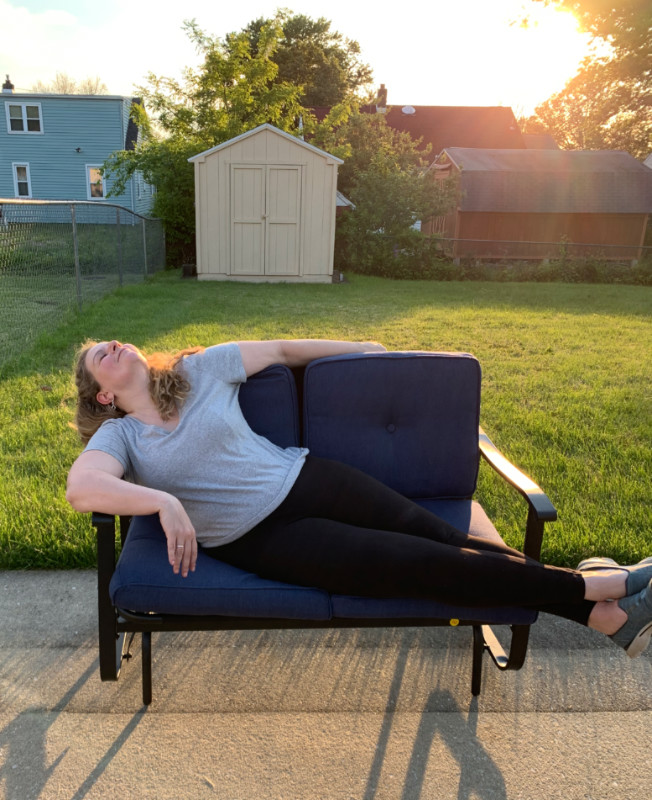 Kim, in a tee and leggings, lounging dramatically across a 2-seat glider in a back yard. It's the golden hour and the sun is streaming across the grass.
