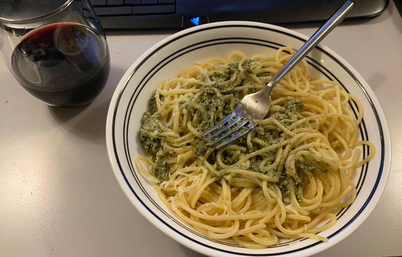 a too-large bowl of spaghetti and pesto, with a glass of red wine on the side