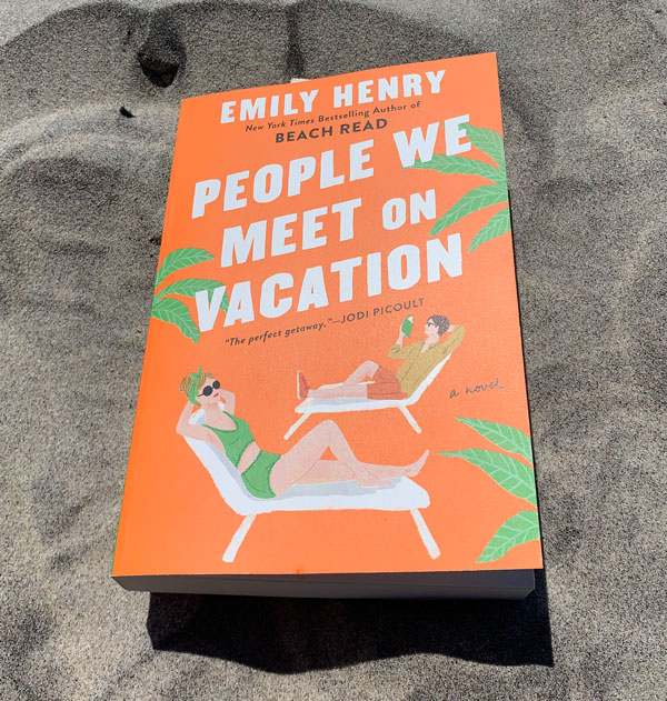 The book People We Meet on Vacation on top of sand.