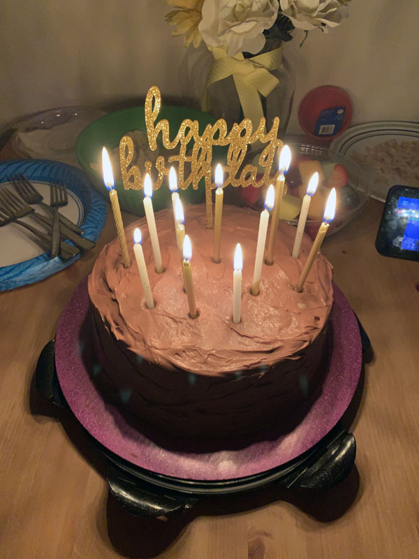birthday cake with gold candles and a gold 'happy birthday' topper
