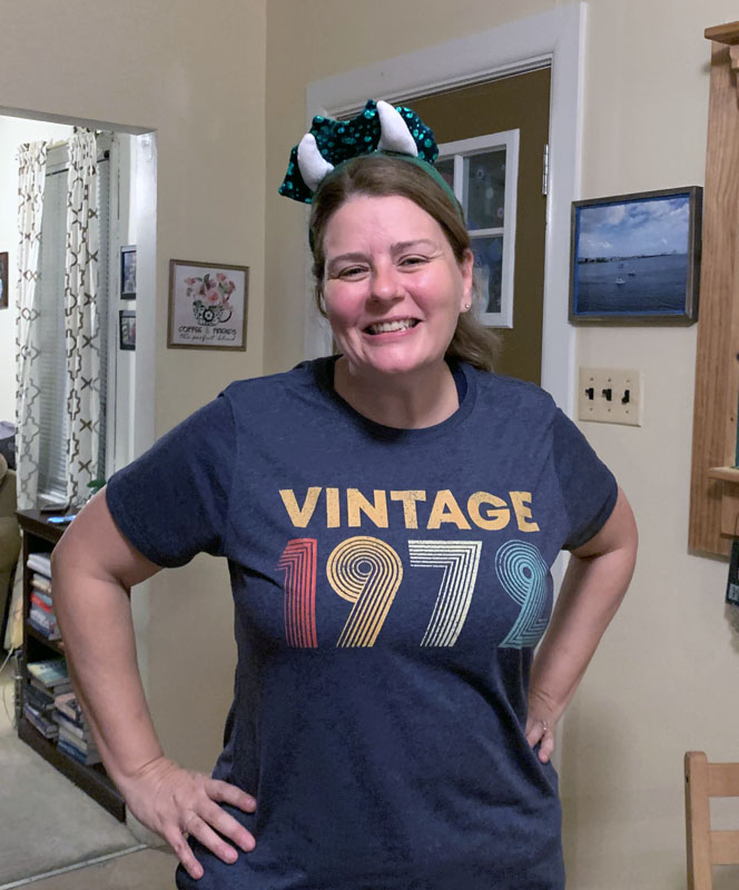 kim in a shirt that says Vintage 1972 and a headband with dinosaur horns on it.