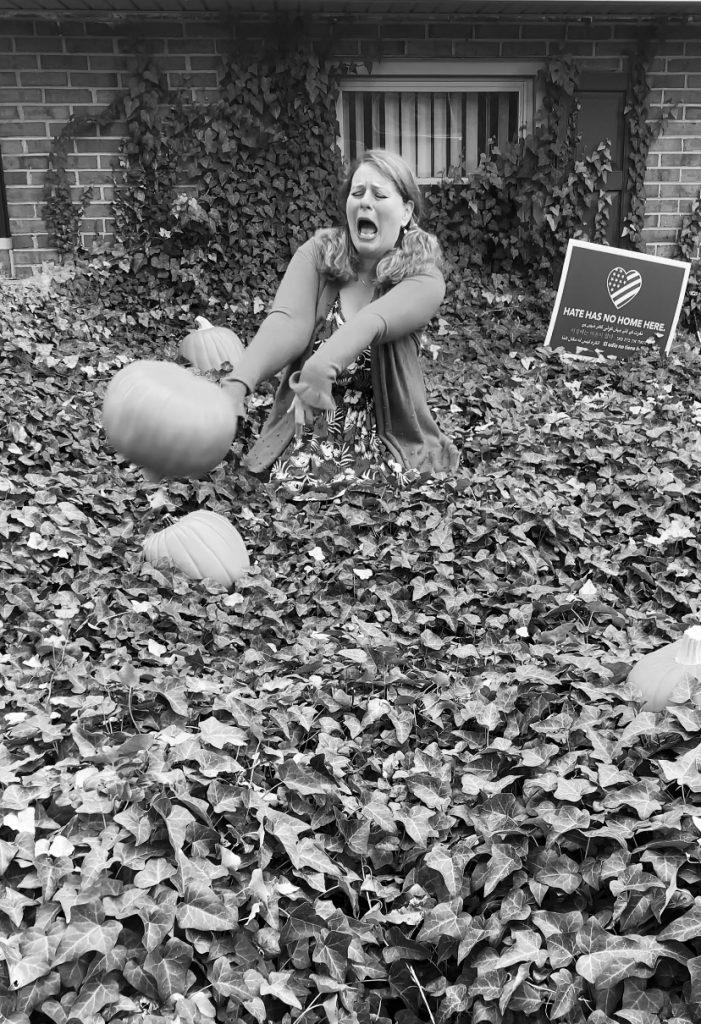 still shot of Kim sitting in her ivy patch tossing a fake pumpkin in autumnal equinox despair