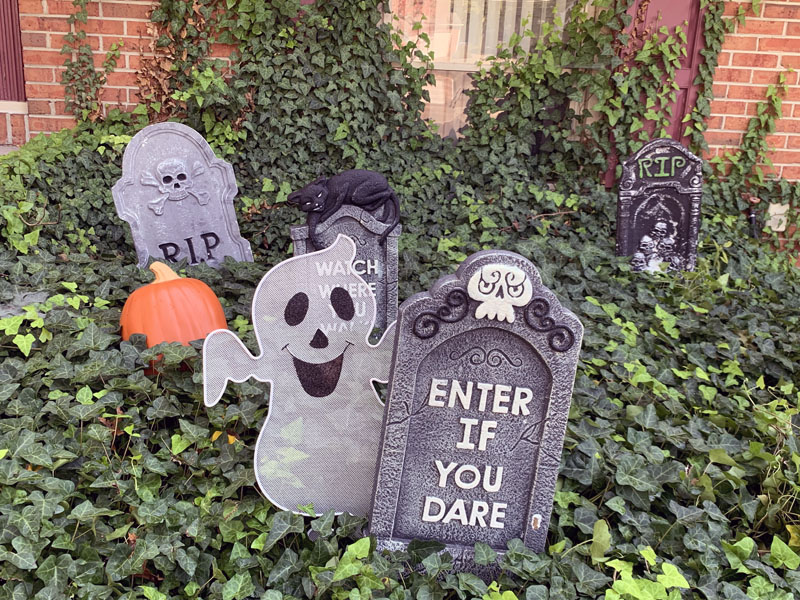 a foam gravestone with a happy wire ghost peeking out from behind it
