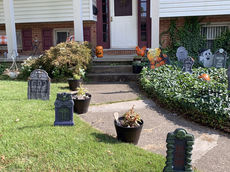 foam gravestones on the other side of a front walkway. there are orange pumpkin decorations on the front porch